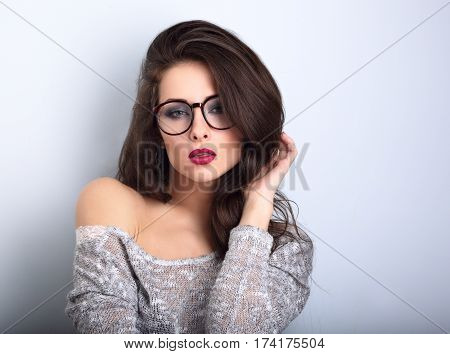 Beautiful Sexy Bright Red Lips Makeup Woman Posing In Gey Blouse On Blue Background. Closeup Portrai
