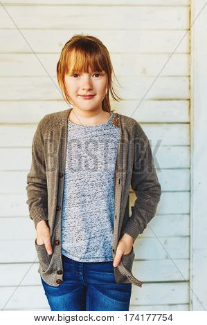 Outdoor portrait of cute little 9 year old girl, wearing grey jacket, standing next to white wooden wall
