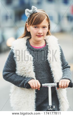 Outdoor portrait of cute 8-9 year old girl wearing grey pullover and white faux fur gilet