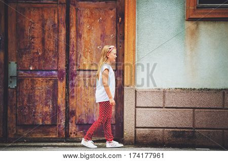 Outdoor fashion portrait of 8-9 year old girl walking down the street, wearing polkadot trousers and white tee shirt, toned image