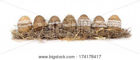 Row Of Handmade Rustic Style Easter Eggs In Moss Isolated On A White Background