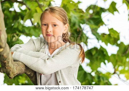 Outdoor close up portrait of cute little 8-9 year old girl leaning on a tree