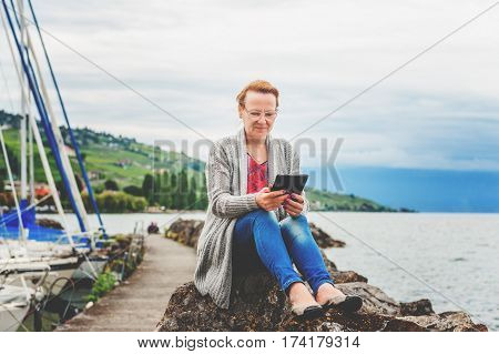 Middle age woman resting by the lake, using tablet pc outdoors