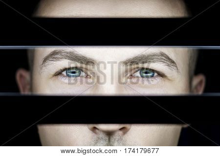 Portrait of a man in dark in light of lamps. Atmospheric art photo of a guy with green eyes. The man's face on the other side of glowing grate light reflection in eyes. Contrast portrait
