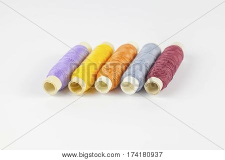Coloured bobbins of thread on white background
