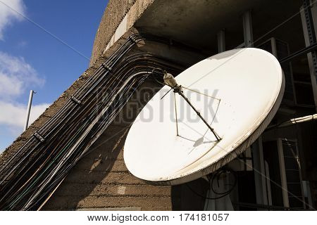 White Satellite Dish With Wires On Telecommunication Tower