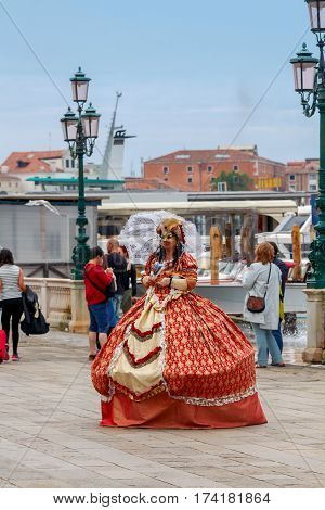 Italy, Venice - 25 May, 2015: Female actor in a medieval costume and mask at the waterfront in Venice. Italy.