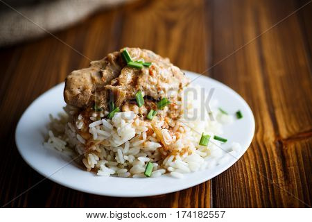 Boiled rice with rabbit meat and sauce on a plate