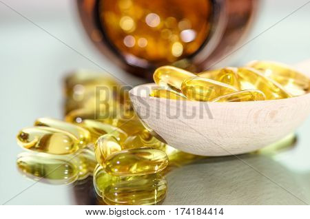 Closeup fish oil dietary supplement. Wooden spoon of oil fish capsules. Omega 3 pills fish oil capsules. Fish oil bottle on background