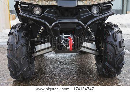 Headlights of black ATV quadbike isolated on city pavement, close up, horizontal