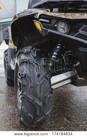 Black ATV quadbike isolated on city pavement, close up, vertical