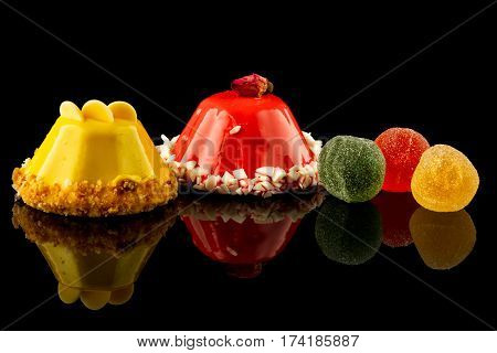 colorfull sweet cake on a black background, reflection.
