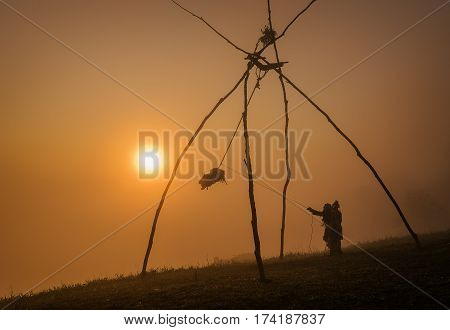 Tribal swings are sitting on a mountain with sun light . people playing with the wooden swing during the mountain