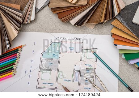 house plan with palette of colors and wooden sampler.