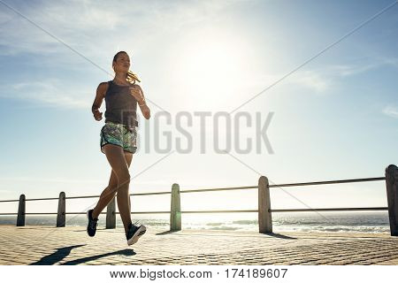Outdoor shot of fitness young woman jogging along the beach. Female runner running outdoors on seaside promenade.