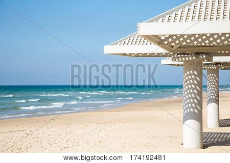Beach sea and white sunshades on sunny day. Travel and vacation concept.