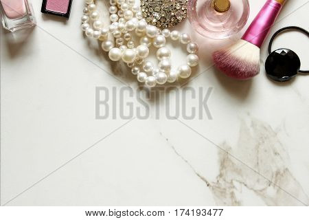 Top view of bathroom vanity with pink make up, vintage jewelry, perfume and hair tie. Open marble space for copy.