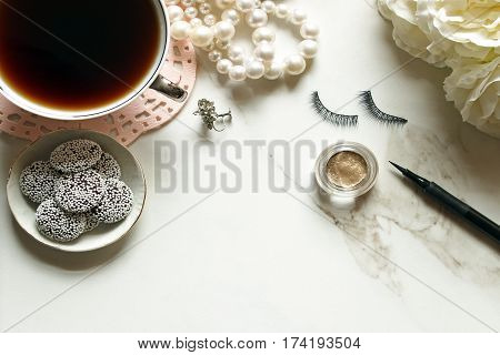 Chic and elegant styled bathroom vanity with coffee, candy, pearls, earrings, make up and flower. Open white marble for copy.