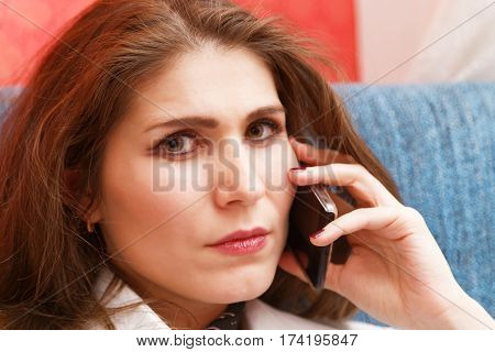 Portrait young skeptical unhappy woman with a serious expression talking on smartphone and looking at camera