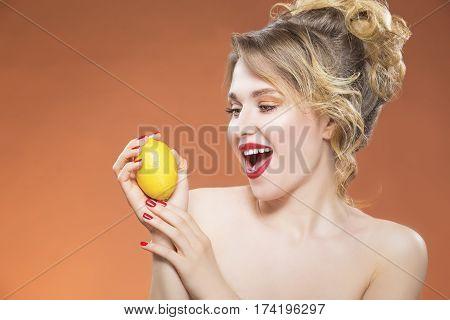 Sensual and Sexy Fruit Series. Positive Playful Caucasian Naked Girl Posing With Yellow Lemon Fruit. Against Orange Background.Horizontal Image