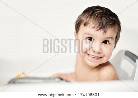 a happy child bathes in a bathroom. Little baby having soapy bath at home