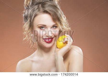 Sensual Fruit Series. Portrait of Alluring Sexy Caucasian Blond Girl With Lemon. Posing Against Orange Background. Horizontal Image Orientation