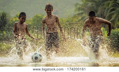 Childrens play soccer in the river .
