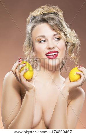 Sensual Fruit Series. Portrait of Alluring Sexy Caucasian Blond Girl With Two Lemons. Posing Against Orange Background.Vertical Image Orientation