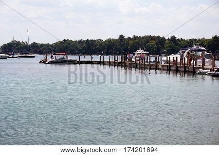 HARBOR SPRINGS, MICHIGAN / UNITED STATES - AUGUST 4, 2016: People walk along the courtesy dock at the Harbor Springs Municipal Marina.