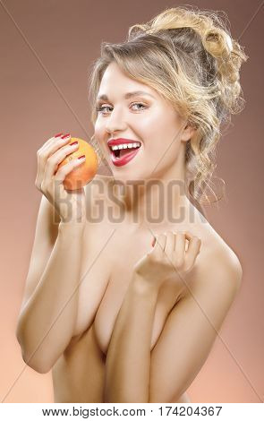 Sexy and tanned Smiling Caucasian Blond Girl with One Orange Fruit in Hand. Posing Against Color Background. Vertical Image Orientation