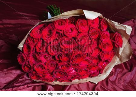 Big bouquet of red roses. Texture colors. A  bouquet gift for a wedding birthday Valentine's Day. Bouquet of red flowers.  Bouquet on red cloth. Beautiful bouquet
