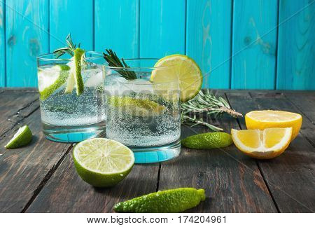 Alcoholic drink gin tonic cocktail with lemon rosemary and ice on rustic wooden table copy space