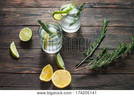 Alcoholic drink gin tonic cocktail with lemon rosemary and ice on rustic wooden table