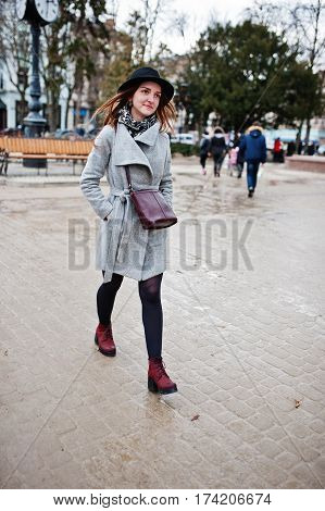 Young Model Tourist Girl In A Gray Coat And Black Hat With Leather Handbag On Shoulders Posed At Str