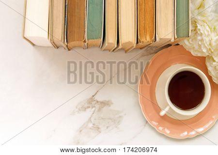 Styled top view of a desktop with vintage book stack, flowers and coffee against  white marble open space.