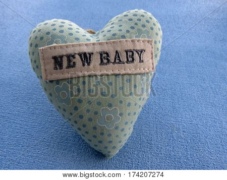 Small blue patterned pillow on a blue background with the words 'new baby' sewn on the pillow
