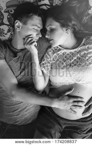 Beautiful Pregnant Wife Holding Hands On Belly With Helpful Husband, Future Parents Lying In Park, T