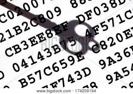 A sheet with encrypted data with a shadow of old-fashioned key