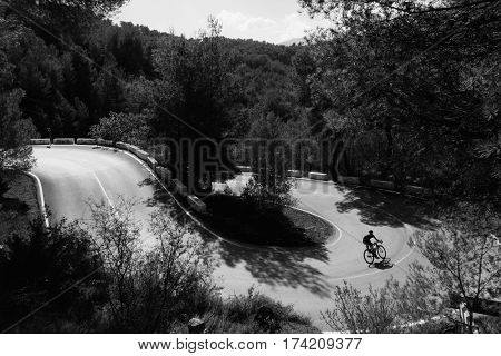 A black and white photo of a cyclist descending a switchback turn