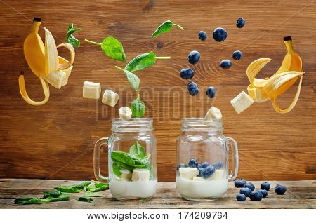 Spinach banana and blueberry banana smoothie with flying slices on a wood background.
