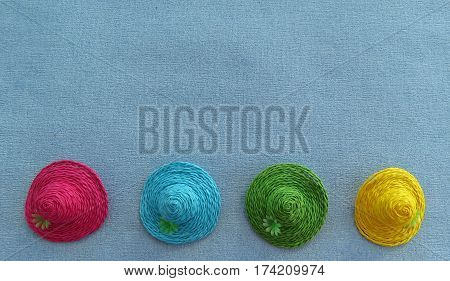 Four colourful Easter bonnets arranged in a row on a blue background with space for text, suitable for Easter, Mothers's Day or birthday occasions