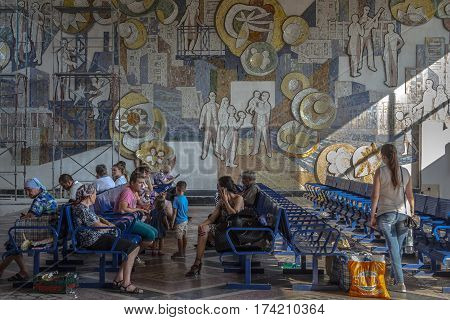 CHISINAU MOLDOVA - AUGUST 11 2015: People sitting in the waiting room of the Chisinau bus station waiting to board an intercity bus. A communist fresco can be seen in the background