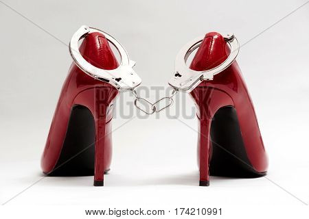 Handcuffs and sexy red high heels on white background. bdsm