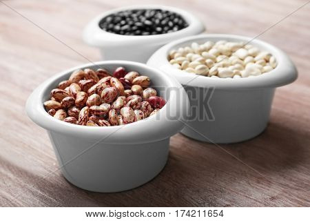 Assortment of haricot beans in bowls on wooden table, closeup