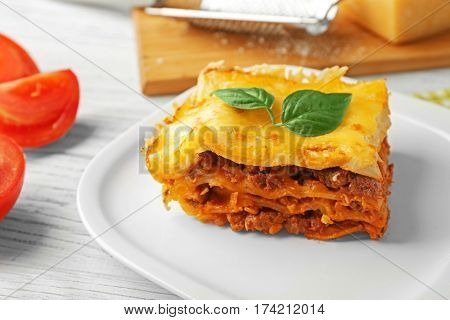 Plate with delicious lasagna on table, closeup