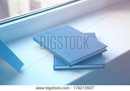 Hardcover books on windowsill