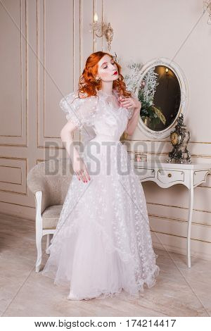 Woman princess with long red curly hair in a white vintage wedding dress with white pearl earrings on her ears. Red-haired girl  princess with pale skin blue eyes a bright unusual appearance in the luxurious bedroom. Princess in white gown