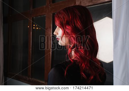 Beautiful woman with red hair and natural make-up and pale skin. A woman in a black retro dress. Model posing in studio. The unusual appearance. Insidious wicked witch woman. Redhead woman. Woman in studio. Gothic woman