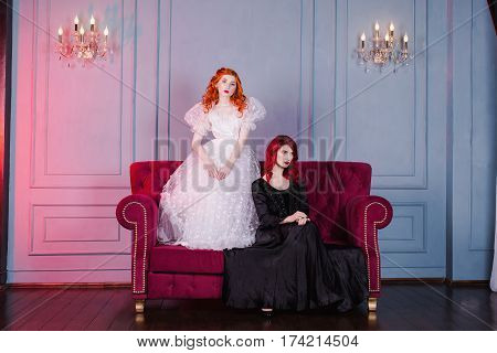 Two girls with red hair in retro dress in the bedroom. Femme fatale in a black dress and nice girl in white wedding dress. Fairy and Witch. Model posing in studio. Historical renaissance dresses.