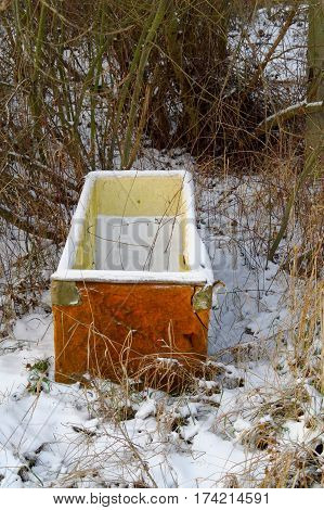 old damaged ejected snow covered fridge in the forest